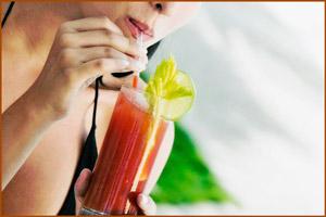 Девушка пьет сок из помидоров